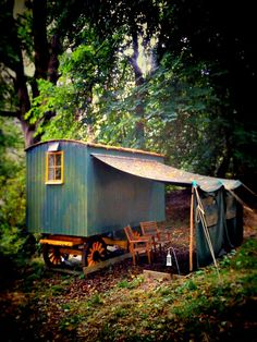 Here's one with a shade attached -- pop a table large enough for family & friends under there, set up a little kitchen by the fire, and presto! Shepherds hut with awning - down by the pond.