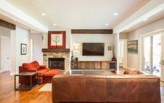 canapé en cuir marron, fauteuil orangé et tv à côté de la cheminée