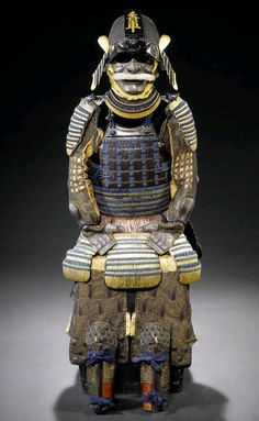 Composite Dangaye Do Tosei Gusoku. Edo Period, 18th century. Sixty-two-plate ko boshi bachi Momoyama period kabuto with a tosei mabisashi deeply embossed with eyebrows black lacquered, A ni mai dangaye do, the upper section of brown lacquered iyozane the lower of gold lacquered kiritsuke kozane, the kusazuri matching. Kosode of kiritsuke kozane, russet lacquered oda gote, ikada haidate and shino suneate matching. Laced overall in dark blue with the yurugi ito in mauve.