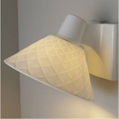 A tapered wall light made in natural white fine bone china, exudes quality. Handmade in the UK, the shade features textured diamonds which contrasts with the smooth and glossy wall bracket. We love this light in any room. It can be dimmable when teamed with a suitable bulb and dimmer switch to help control the desired ambience.