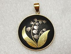 Beautiful pendant from Amita in Japan done in the black and gold damascene finish with a lily of the valley flower design.    1 inch in diameter.    No