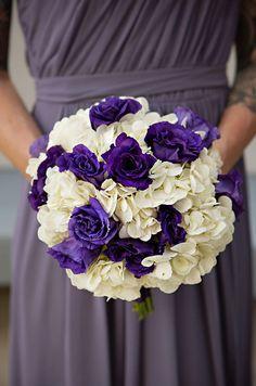 Full bridesmaid bouquets feature dark purple roses with fresh white hydrangeas.
