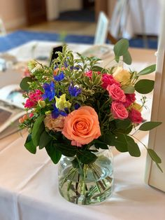 A colourful posy in a simple glass vase to brighten up a guest book table