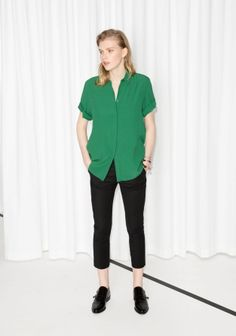 Made from fabric with crisp feel, this buttoned top features short folded sleeves and pointy collar.