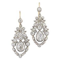 A pair of late Georgian open-work diamond drop earrings, set with three graduating old brilliant-cut diamonds, suspended from two old brilliant-cut diamonds within a diamondset scroll design, circa 1830.