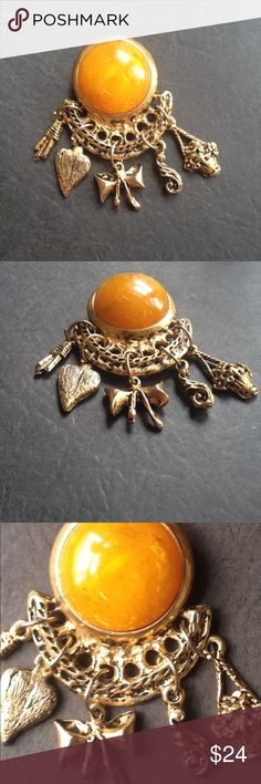 "Vintage Dangling Charms Brooch Vintage, antiqued, gold toned brooch featuring a round, egg yolk, faux Amber cabochon with an ornate ""honey comb"" crescent from which hang 5 adorable charms. Not sure exactly if it is 60's, 70's or 80's. Heavy, well constructed, 2&1/2"" tall x 1&1/2"" wide. Dangling 3D basket o flowers, heart, bow, tassel & paisel. Truly charming adornment. Vintage Jewelry Brooches"