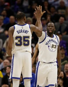 Golden State Warriors forward Draymond Green, right, gets a high-five from teammate Kevin Durant after scoring and getting fouled during the second half of an NBA basketball game against the Sacramento Kings Friday, Feb. 2, 2018, in Sacramento, Calif. The Warriors won 119-104. (AP Photo/Rich Pedroncelli)