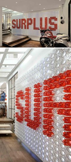 Plastic Drink Bottles Were Reused To Create A Giant Logo For This Shop (Bottle Display Ideas) Display Design, Store Design, Wall Design, Display Ideas, Environmental Graphic Design, Environmental Graphics, Wayfinding Signage, Signage Design, Art Expo