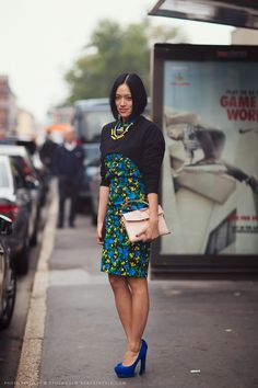 Tiffany Hsu in a floral dress, cropped sweater, and blue suede heels.