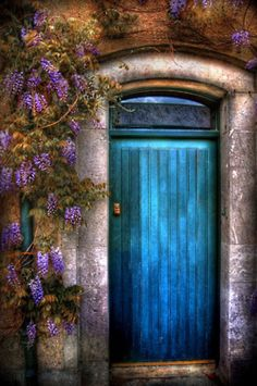Turquoise door with purple wisteria and rustic stone work. Take me away!