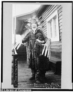An Eskimo medicine man stands over a sick boy