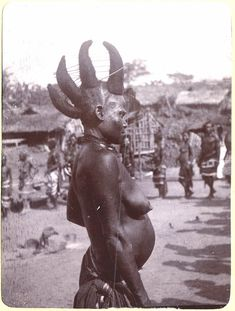 Photograph (black and white); from an album; women's dance at Awakande. Woman standing in the foreground; wearing necklaces and lower wrap, her hair is elaborately dressed in the shape of four cattle horns supported with a series of strings to keep them in place. In the background is a line of women and several thatched huts. Cross River, Obubura Hill District, Nigeria. 1904.  Gelatin silver print