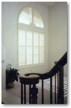 Custom Wood Shutters on an arched-top window.