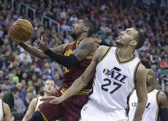 Cleveland Cavaliers guard Kyrie Irving, left, shoots as Utah Jazz center Rudy Gobert (27) defends during the second quarter of an NBA basketball game Tuesday, March 15, 2016, in Salt Lake City