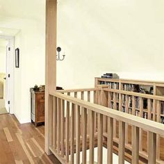 A long run of surface-mount, low bookcases transforms the space at the top of the stairs into a library. The second-to-last one on the right (not shown) is set on casters, so it can be pulled out to access crawl-space storage