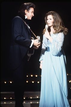 "June Carter was born into a musical family, performing with the Carter Family as early as age 10. She met singer Johnny Cash in 1950 backstage at the Grand Ole Opry, their first duet came in 1964 with ""It Ain't Me Babe."" The two performed together for years before Cash proposed in front of a live audience in 1968. - HarpersBAZAAR.com"