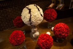 red carnation pomanders with a larger pomander designed to look like a baseball