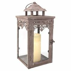 """Candle lantern with iron filigree detail.Product: Candle lanternConstruction Material: Iron and glassColor: Distressed ivoryAccommodates: (1) Pillar candle - not includedDimensions: 13.3"""" H x 6.3"""" W x 6.3"""" D"""