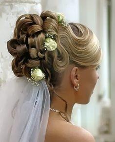 Peinado de novia con moño alto de mechones ensortijados adornado con flores