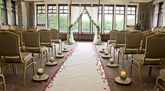 Birch pole archway with ivory drapes and artificial wisteria, wooden slices with storm lanterns, pillar candles and artificial moss, and white aisle carpet with rose petals. By www.stressfreehire.com #venuetransformers - photo by Weddings at Silvermere