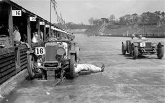 As another car races past, a mechanic lies with his legs on the track as he works on a Lea-Francis 1496S cc that was retired from the race due to engine issues at the Brooklands JCC Double Twelve. Note the wooden pit lane huts