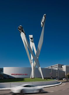 Three sports cars appear to soar up into the sky outside auto brand Porsche's museum in Stuttgart as part of this sculpture by British artist and designer Gerry Judah.