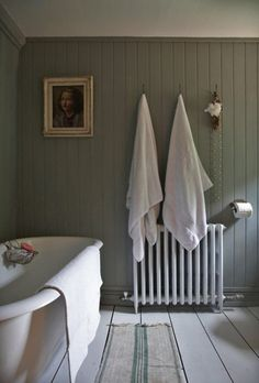 white suite backed with grey tongue and groove wall. Towels hanging above a traditional radiator