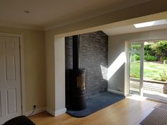 Penman Lunen woodburning 5kw stove. Black limestone hearth and split face tiled backing.