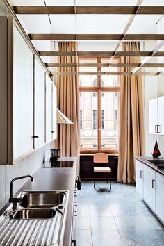 Beige-peach curtains soften an otherwise sleek kitchen in Emmanuel de Bayser's modernist apartment in Berlin.
