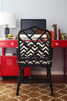 Gorgeous office with Ballard Designs Macau chair in black with white & black zigzag chevron cushions, glossy red desk with turned legs, gold horse head bookends, red locker, horse head lamp and brown Pottery Barn Moorish Tiles Rug.