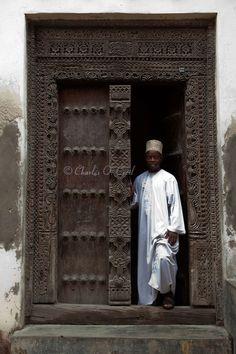 Africa | Zanzibar, Tanzania. An Arab-style Doorway in Stone Town. An African Zanzibari Wearing Traditional Kanzu and Kofia (Hat) Stands in the Doorway. | ©Charles O Cecil
