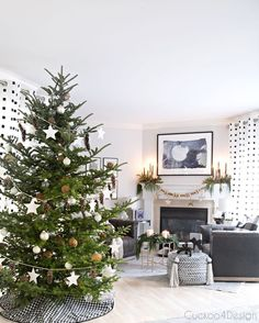 Modern European Eclectic Christmas Tree with pinecones, white stars, clear Christmas balls and white Christmas balls on a real untrimmed fir tree | blue, white and black fireplace area with leather swivel chairs via @jakonya