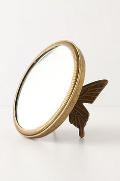 Brass vanity mirror propped up by butterfly wings (Anthropologie).