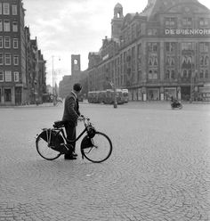 1950. Solex-moped rider on an emplty Dam square in Amsterdam. #amsterdam #1950 #Dam