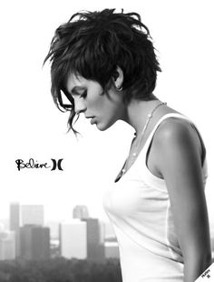 Shaved sides with a defining middle part raised in a medium puff. The rest of the hair is pulled up in a high bun on the crown. The shade here is gray with a purple tinge. This funky hairstyle for short hair has bluish white hues with a darker tone of color near the roots is simply stunning.