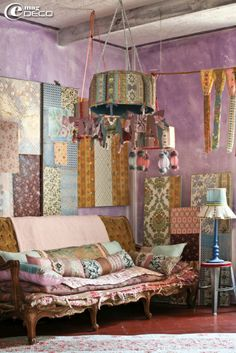 Artistic French boho bohemian living room lounge with scrappy wall decor and pendant light.