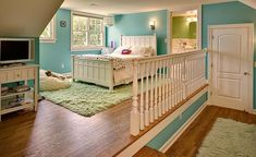 Lovely two level girl's room with blue walls features a striped paper lantern above the white paneled bed atop a green shag rug beside a shag bean bag.