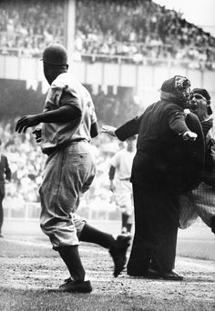 """Yogi Berra takes issue with the umpire's """"safe"""" call after Robinson's electrifying steal of home in Game 1 of the 1955 World Series. Six decades after it was taken, this picture reminds us of what an intense competitor Berra, like Robinson, really was. Today, he's often regarded a cuddly old ambassador for baseball. But back then, when the game was on the line, Yogi Berra was a warrior. (Grey Villet—Time & Life Pictures/Getty Images)"""