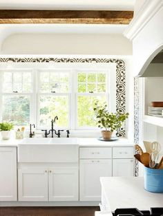 White kitchen with farmhouse sink and beautiful window's.