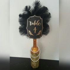 DIY Great Gastby Centerpiece - wedding or anniversay party. Black and gold with feathers and pearls.