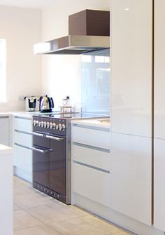 The Mercury range cooker in purple haze  finish really stands out against the stylish gloss white units in this modern kitchen.