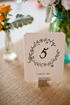 The simple yet sweet table numbers featured a vintage-inspired sketch of a wreath. | Photo by Matushek Photography
