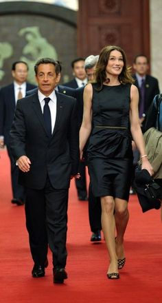 French President Nicolas Sarkozy, his wife Carla Bruni-Sarkozy, and French Ecology, Energy and Sustainable Development and Climate Negotiations State Minister Jean-Louis Borloo (L) arrive for a dinner with Chinese President Hu Jintao (unseen) at the Great Hall of the People on 4/28/10 in Beijing.
