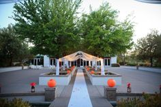 aisle and waterscape decorated with orange lanterns, springtime wedding with pops of orange