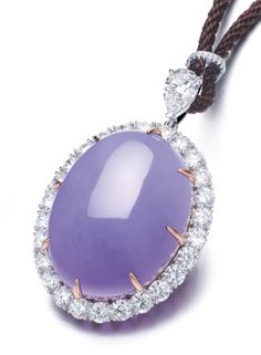 A MAGNIFICENT JADEITE AND DIAMOND PENDENT NECKLACE, BY CHOW TAI FOOK Suspending a thick high domed oval jadeite cabochon of even rich lavender colour and very good translucency, within a brilliant-cut diamond surround, to the pear-shaped diamond surmount, joined to a brown silver cord, mounted in 18k white and rose gold, cabochon approximately 37.1 x 28.2 x 14.1 mm, 78.0 cm long With maker's mark for Chow Tai Fook