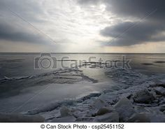 The late afternoon winter sky casts a glow on the frozen water of Lake Erie.