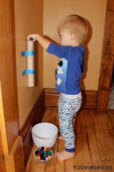 11.) Tape a paper towel roll to the wall to make a simple game for your toddler.
