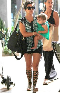 Those shoes again: Kourtney Kardashian, here in July, loves her gladiator style, knee high sandals and is pictured in them often