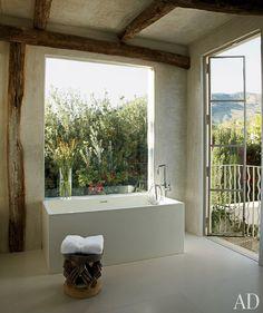 Rustic space has modern tub under window of nearly equal width; Richard Shapiro