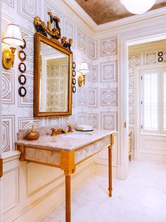 geometric wallpaper, marble sink console, gilded mirror and sconces // bathrooms
